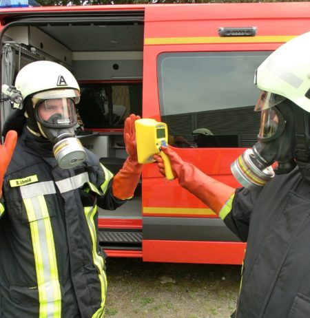 A fireman checking another one's contamination rate with a hand-held contamination monitor