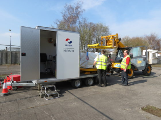 Two men working with a High Resolution Assay Monitor-trailer mounted system and a worksite vehicle