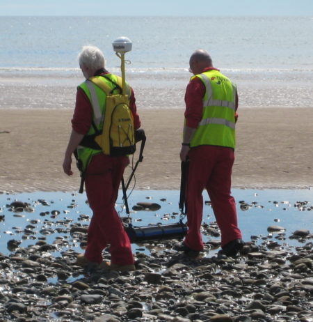 Two workers using a portable Gamma-Ray Spectrometer to monitor radiations on a beach