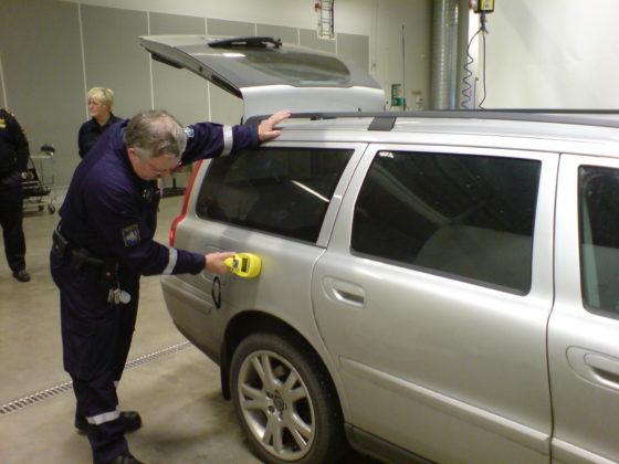 A man using a portable contraband detector