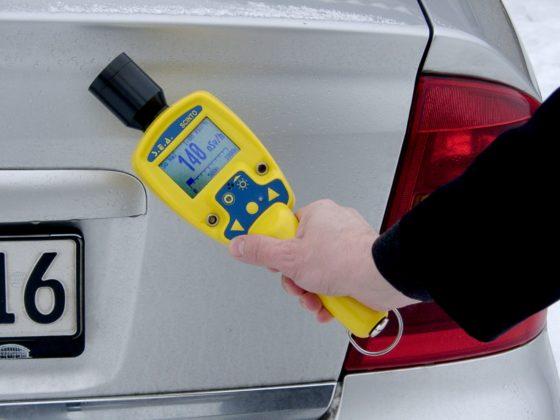 Someone using a high-sensitive gamma radiation monitor on a car