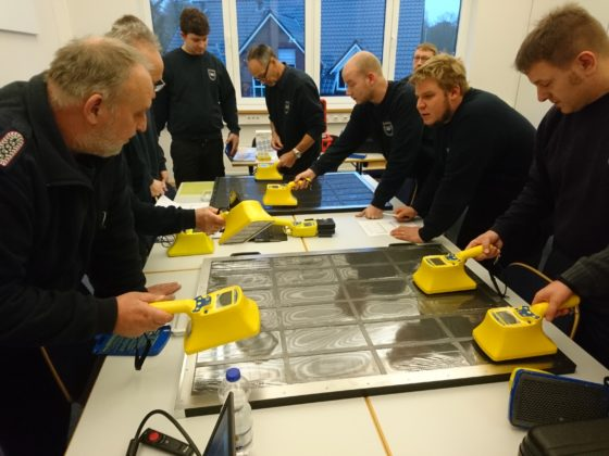Radiation safety personnel are training by searching contamination on a drawer